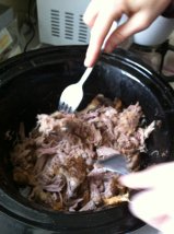 We put it in the crock pot overnight (flipping it a few times).  The next day it was soft enough that we could easily shred it with a couple of forks.  We drained the grease (saving some of it), removed the bone, and then shredded the pork.