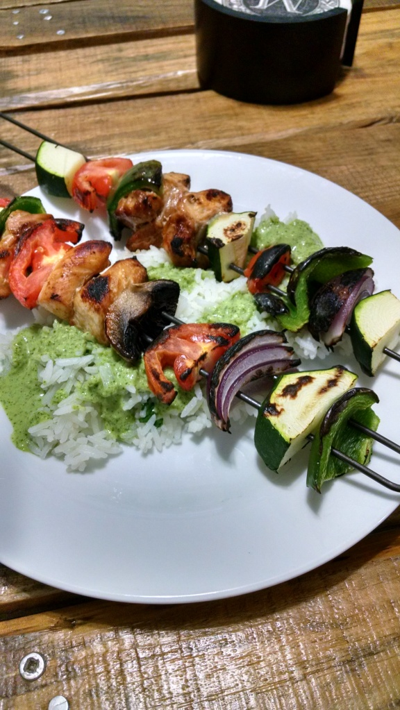 chicken and vegetable kabobs over rice with green sauce